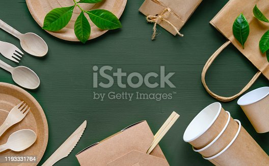 Eco-friendly disposable tableware made of paper on a green wooden table. Wooden spoons, fork, knive, with paper cups, plates, box, bamboo chopstic.