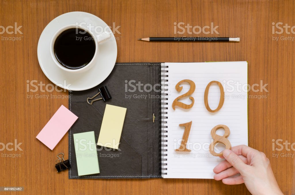 Recycled notebook with woman hand putting 2018 letters on empty paper note surrounding with black coffee in white cup; yellow pink green sticky pads; pencil & paper clips on dark wood background space stock photo