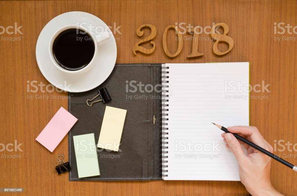 Recycled notebook with woman hand writing in the paper note surrounding with black coffee in white cup, 2018 letters, yellow pink green sticky pads, pencil & paper clips on dark wood background space stock photo