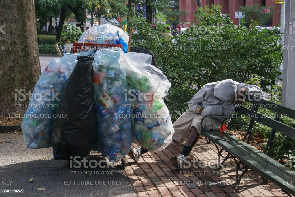 A recycler sleeps in the park after a hard night collecting bottles and cans stock photo