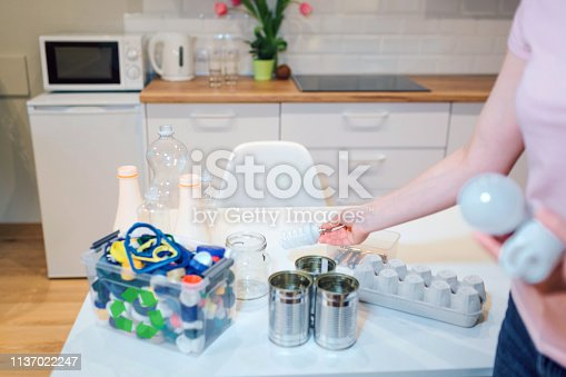 1137022282 istock photo Recycling. Assorted of metal, plastic, glass, paper, electronic waste on kitchen table 1137022247