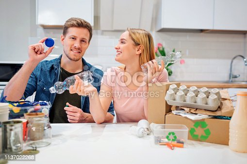 1137022221 istock photo Recycling. Aware young family sorting empty plastic bottles and lids while sitting at the table with other waste at home 1137022268