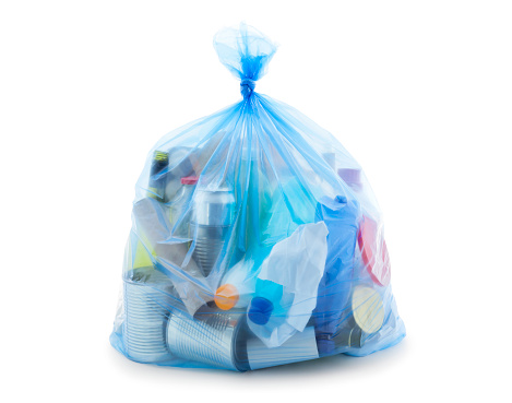 Blue recycling bag full of mixed materials paper, plastic, glass and metal isolated on white