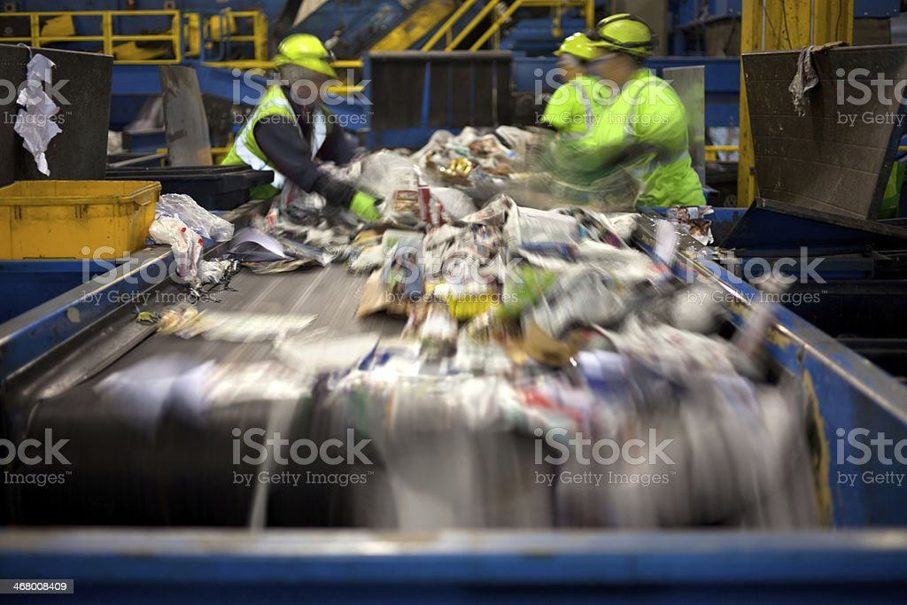 Recycling belt Workers separating paper and plastic on a conveyor belt in a recycling facility Automated Stock Photo