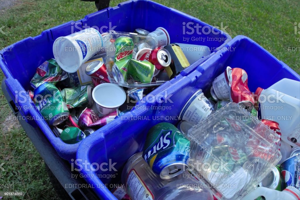 Recycling bins with plastic containers, glass bottles, and aluminum cans stock photo