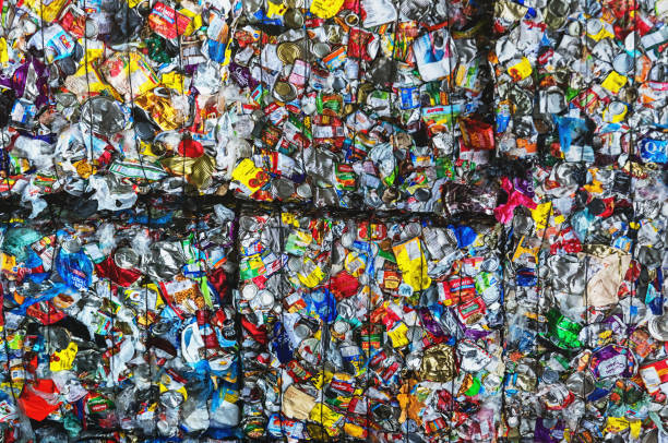 Recycling Centre Bales of compressed plastic bags and dairy product cartons at a recycling centre. bottle bank stock pictures, royalty-free photos & images