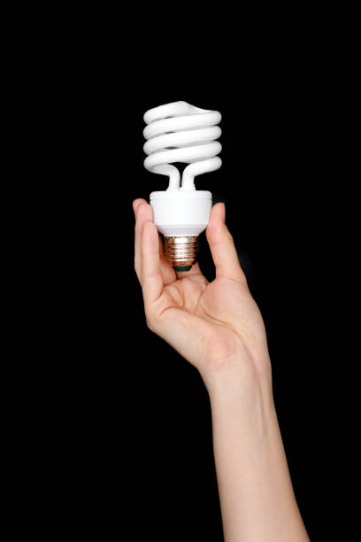 Recycling, electricity, environment and ecology concept - close up of hand holding energy saving lightbulb or lamp. Compact fluorescent light bulb on black background. stock photo