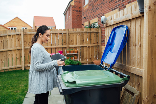 Side view of a pregnant woman disposing of her household recycling into an outdoor bin in her garden. She is in the North East of England.