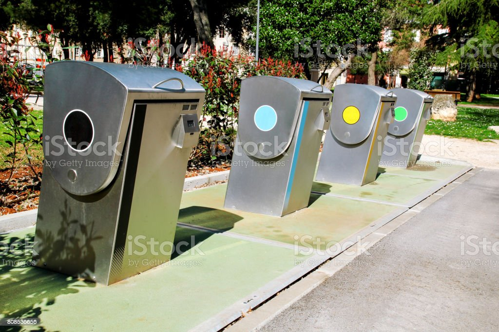 Recycling industry. Modern recycling containers on the city. Refuse bins in traditional europe city. Street recycling containers and trash dumpsters for paper, glass and plastic. Recycle trash bins. stock photo