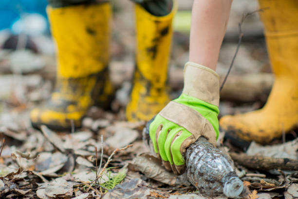Recycling An Ethnic brother and sister are outdoors in a muddy forest. They are wearing casual clothing, rubber boots, and gloves. They are  picking up plastic bottles to recycle. environmental cleanup stock pictures, royalty-free photos & images