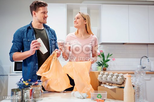 1137022295 istock photo Recycling. Responsible young couple putting empty plastic and paper in garbage bags while looking at each other near the table filled with waste 1137022267