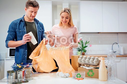 1137022221 istock photo Recycling. Responsible young couple putting empty plastic and paper in garbage bags while standing near the table filled with waste at home 1137022270
