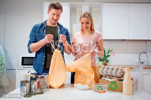 1137022221 istock photo Recycling. Responsible young family putting empty plastic and paper in bags while standing near the table filled with waste at home 1137022289