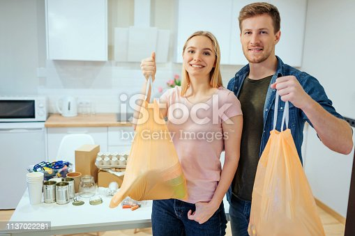 1137022295 istock photo Recycling. Responsible young smiling family holding garbage bags while standing near the table filled with waste at home 1137022281