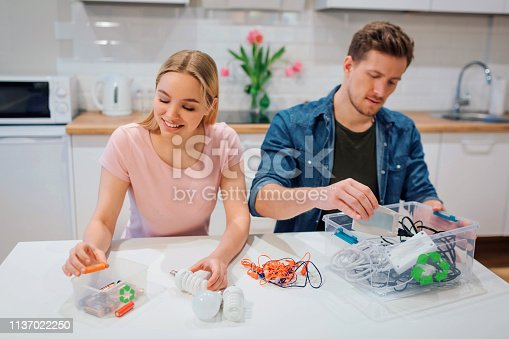1137022221 istock photo Recycling, reuse, energy. Young couple sorting batteries, other electronic waste into containers with recycling symbol while sitting at kitchen 1137022250