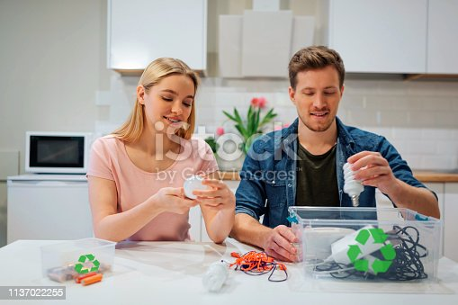 1137022221 istock photo Recycling, reuse, energy. Young family sorting light bulbs, batteries, other electronic waste into containers with recycling symbol while sitting at kitchen 1137022255