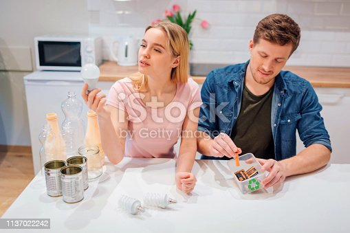 1137022282 istock photo Recycling, reuse. Young couple sorting batteries, light bulbs into small containers with recycling symbol while sitting at kitchen 1137022242