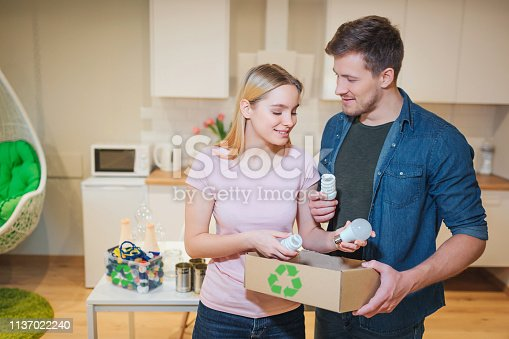 istock Recycling, reuse. Young smiling family putting white light bulbs into paper box with recycling symbol on kitchen background 1137022240
