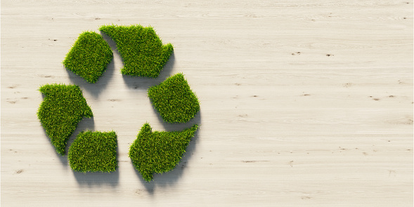 Recycling symbol made of green grass on wood background. Horizontal composition with copy space. Green energy concept.