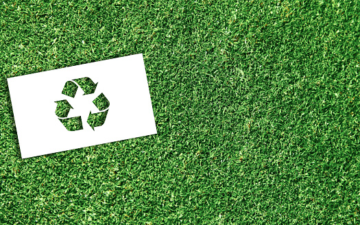 Ecology concept: recycling. Green recycling symbol obtained on perforated white sheet of paper, inside a green grass meadow