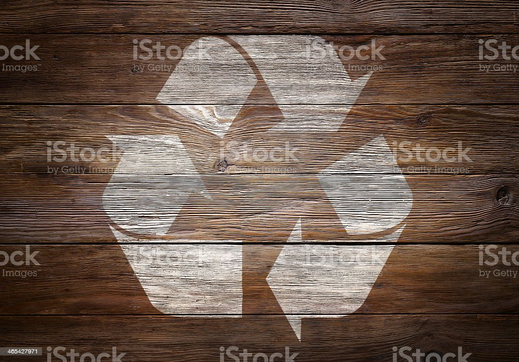 A heavily textured dark, wooden background, with the Recycling Symbol...