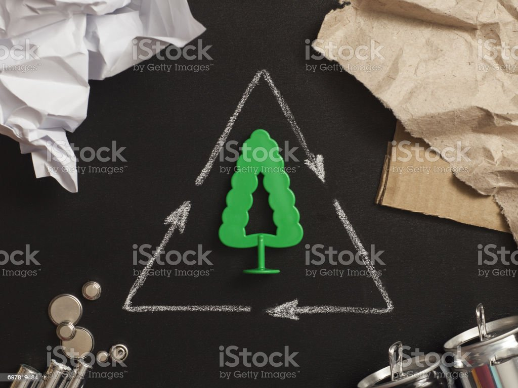 recycling symbol with garbage on black background top view stock photo