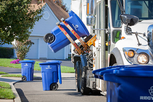 recycling truck lifting up container along neighborhood curb - recycling symbol stock photos and pictures
