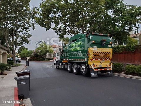 San Ramon, California, United States - August 29, 2019:  Garbage truck or recycling truck from Waste Management traveling through a suburban neighborhood in the morning, San Ramon, California, August 29, 2019.