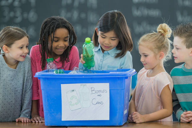 Recycling with Friends A multi-ethnic group of elementary age school children recycle plastic bottles into a blue recycling bin inside a classroom with a blackboard in the background. bottle bank stock pictures, royalty-free photos & images