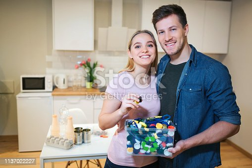 istock Recycling. Young smiling couple holding plastic lids in the container with green recycle icon on kitchen background 1137022227
