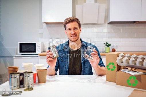 1137022221 istock photo Recycling. Young smiling man is sorting empty glass bottles and metal cans while sitting at the table with other waste at home 1137022259