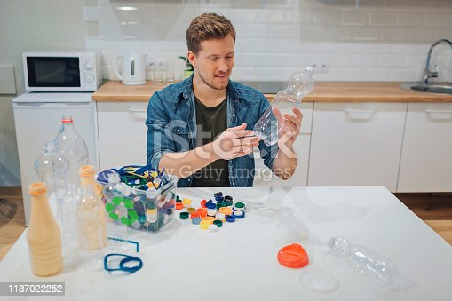 1137022282 istock photo Recycling. Young smiling man is sorting empty plastic bottle and lids while sitting at the table 1137022252