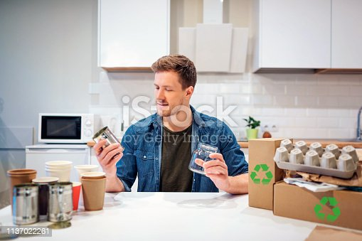 1137022221 istock photo Recycling. Young smiling man is sorting metal cans and glass bottles while sitting at the table with other waste at home 1137022261
