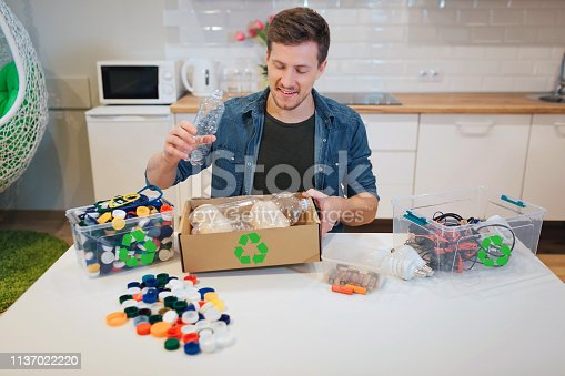 1137022221 istock photo Recycling. Young smiling man putting emty plastic bottle into paper box while sitting at the table with other waste at home 1137022220