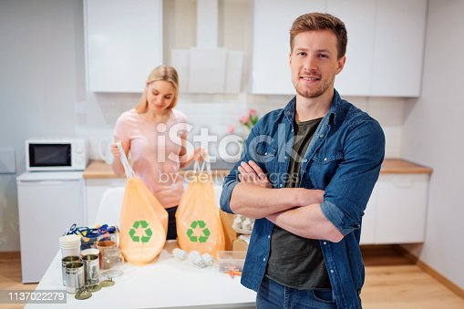 1137022221 istock photo Recycling. Young smiling man standing after recycling while his girlfriend holding garbage bags with recycle symbol at the kitchen 1137022279