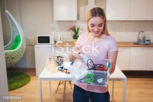 1137022221 istock photo Recycling. Young smiling woman holding electronic waste in the container with green recycle icon on kitchen background 1137022224