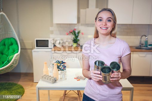 1137022221 istock photo Recycling. Young smiling woman holding metal tin cans for reuse on kitchen background 1137022231