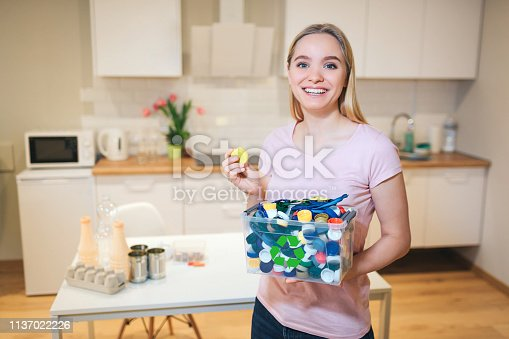 1137022221 istock photo Recycling. Young smiling woman holding plastic lids in the container with green recycle icon on kitchen background 1137022226