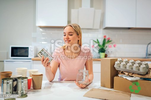 1137022295 istock photo Recycling. Young smiling woman is sorting empty glass bottles and metal cans while sitting at the table with other waste at home 1137022257