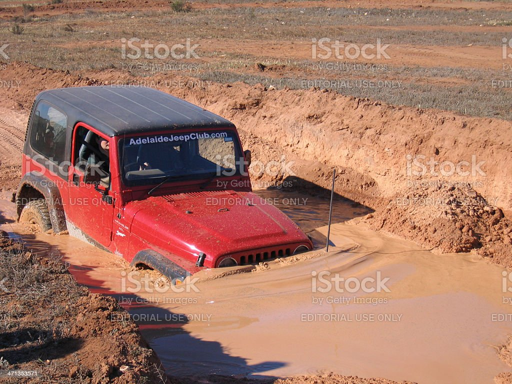Red 1997 TJ Jeep Wrangler drives through a water crossing stock photo