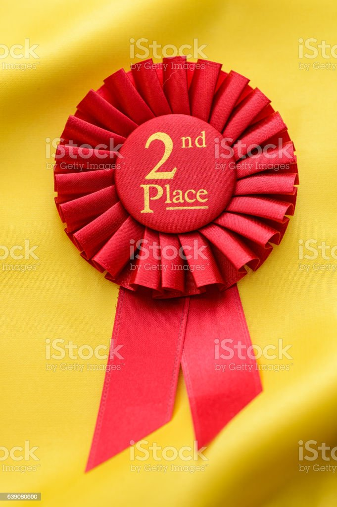 Red 2nd Place winners rosette on gold fabric stock photo