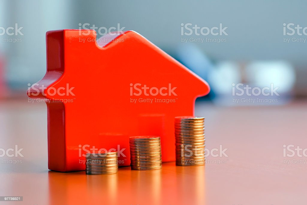 Red 3D house model next to growing stacks of coins stock photo
