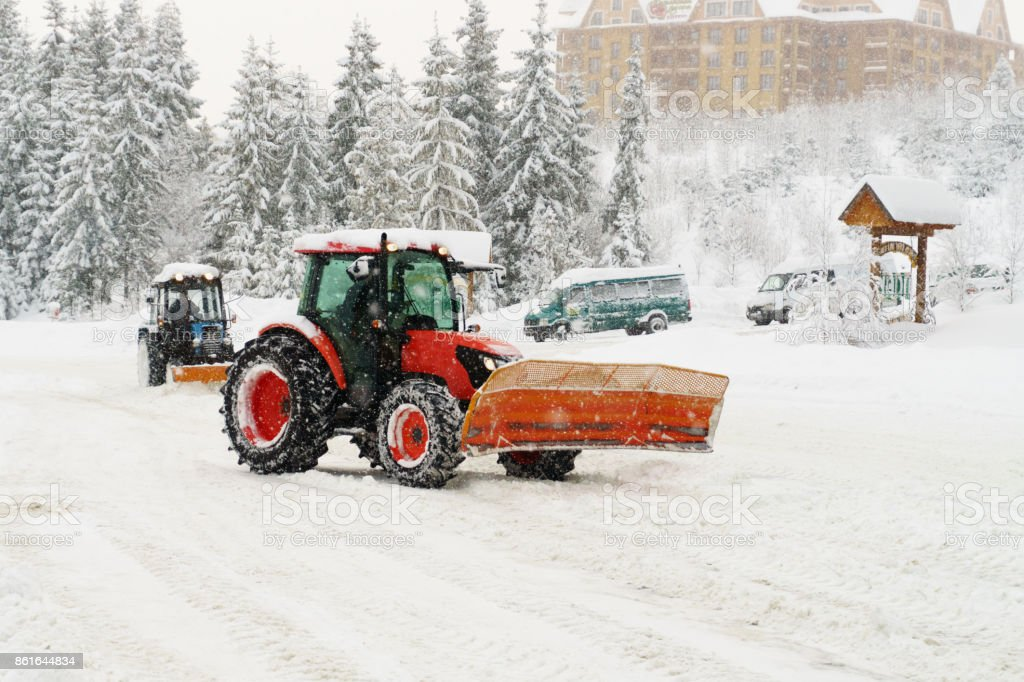 Red abd blue snowblower graders clears snow covered ski resort road in mountains or city street. Winter snowflake snowfall cold fog, mist weather. Horizontal, copy space. stock photo
