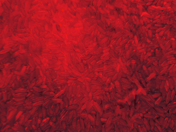 Red abstract background with rice and food colouring stock photo