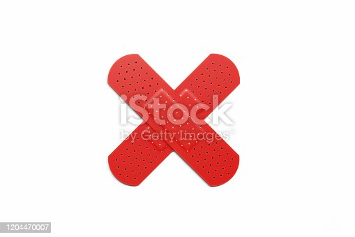 Red adhesive bandage plasters forming a cross on white background, Horizontal composition with clipping path.