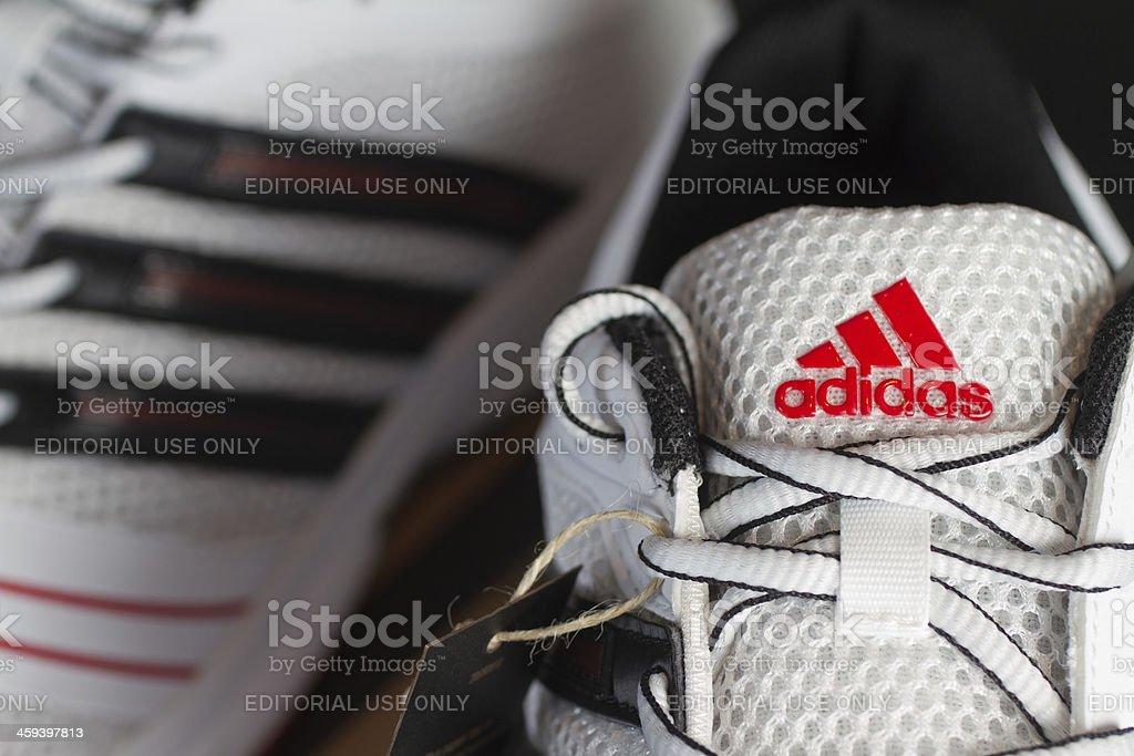Red Adidas logo on white running shoe