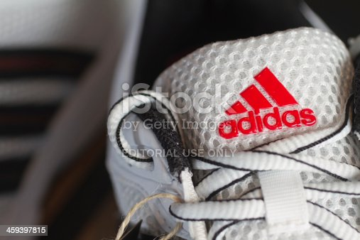 Fuerth, Germany - October 19, 2011: Red Adidas logo on a white nylon running shoe.Adidas AG is one of the leading sports apparel manufacturer in the world with their headquarter in Herzogenaurach, Germany. Adidas is also famous for its distinctive three stripes on the majority of all products.
