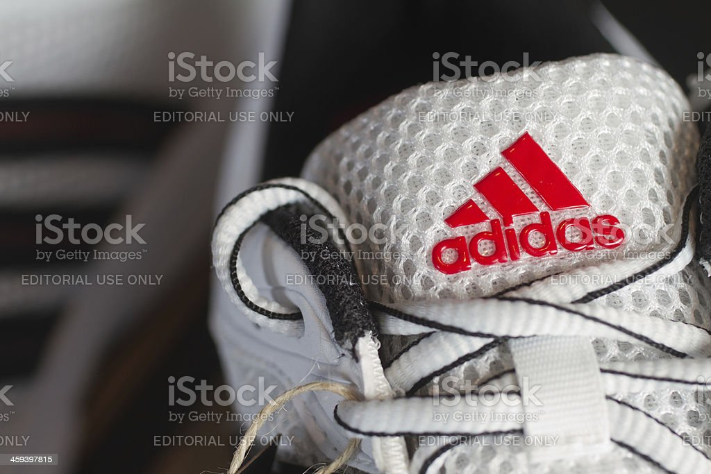 Red Adidas logo on white running shoe stock photo