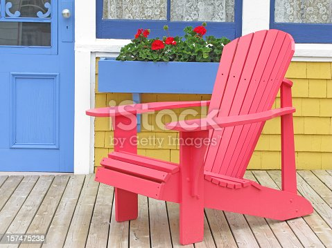 A traditional Adirondak outdoor chair on the porch of a brightly painted wooden house, typical to Eastern Canada. This one was photographed on Prince Edward Island.