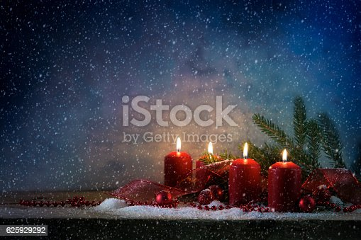 istock red advent candles burning, dark snowy background with copy space 625929292